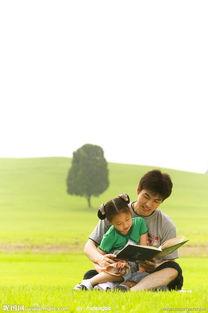 小孩子和爸爸坐在草地上看书图片