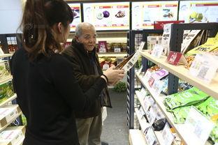 商场工作人员正在给一位老人讲解如何扫码支付可以送货上门的服务.