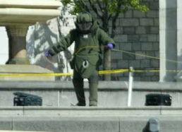 拆弹专家正在处理两个黑色手提箱.