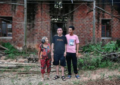 张玉环(中)和儿子与母亲在自己入狱前的住处前留影(8月6日摄).