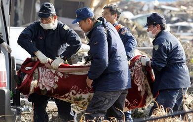 3月13日,仙台,救援人员在运送遇难者遗体.