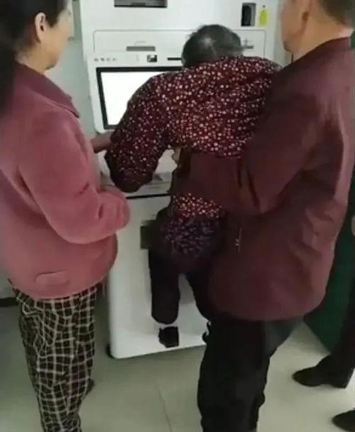 老人在银行被抱起进行人脸识别。
