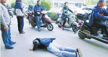 老人摔倒后,几位路人帮忙拦住车流